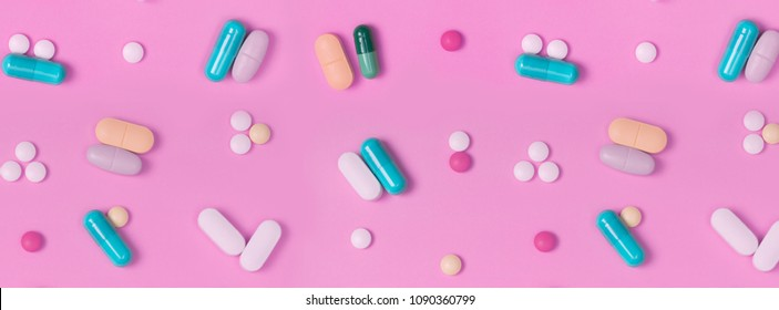 banner white pills round and oval and multi-color capsules on a pink background.  top view. medicinal drug. biohacking concept. pattern