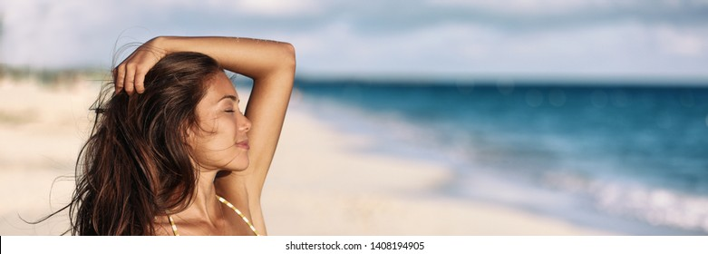 Banner woman relaxing touching her hair wellness summer holiday ocean beach panoramic background on tropical Caribbean summer vacation panorama. Asian girl breathing clean air.
