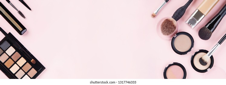 Banner of woman's cosmetics on pink background. Women's secrets. Decorative cosmetics: highlighter, concealer, rouge, palette with eye shadows and brushes for face make up, face sculpture. Copy space