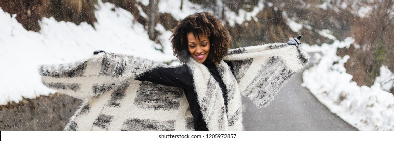 Banner of young black woman dancing and having fun under the snow in cold winter.