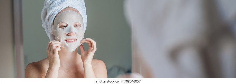 BANNER Young red-haired woman doing facial mask sheet. Beauty and Skin Care Concept Long Format.