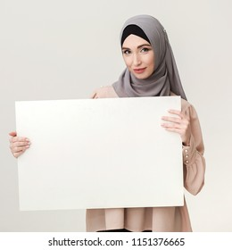 Banner for your adverticement. Arabian woman in hijab showing white placard, copy space