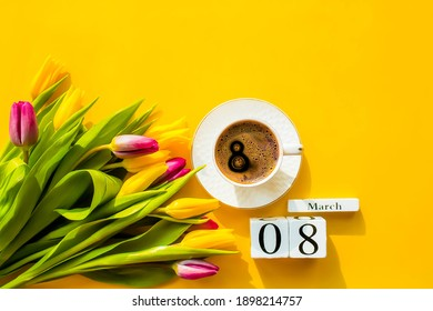 Banner.A cup of hot, morning coffee and a bouquet of yellow-lilac tulips on a bright yellow background. View from above. Close-up. Copy space for text. The concept of holidays and good morning wishes.
