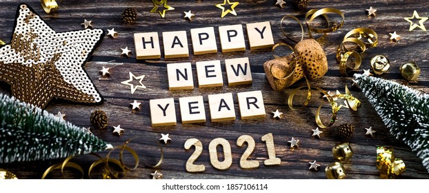 Banner.Happy New Year 2021. A symbol from the number 2021 with Golden balls, stars, sequins and a beautiful bokeh on a wooden background. The concept of the celebration. - Shutterstock ID 1857106114