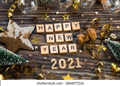 Banner.Happy New Year 2021. A symbol from the number 2021 with Golden balls, stars, sequins and a beautiful bokeh on a wooden background. The concept of the celebration. - Shutterstock ID 1864077226