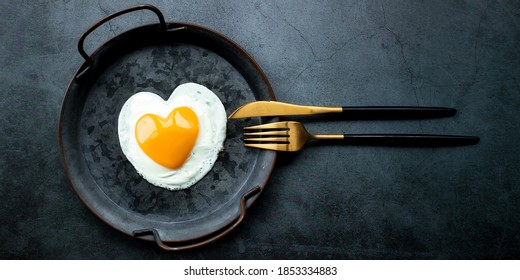 Banner.Homemade fried egg in a vintage pan and stylish cutlery on a dark background. Heart-shaped yolk.View from above. Copy space for text.