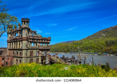 Bannerman Island Castle with view of Hudon Valley and train on rail line. Bright yellow spring flowers edge foreground and Hudson Highland mountains fill the background.