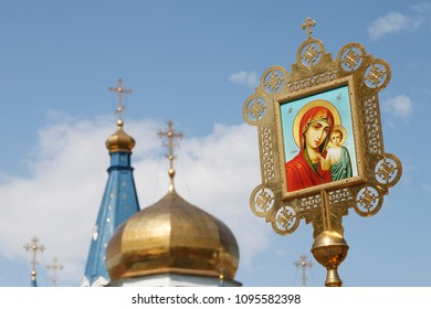 banners, icon of our lady of Kazan on the background of the blue sky and the domes of the temple, copy space