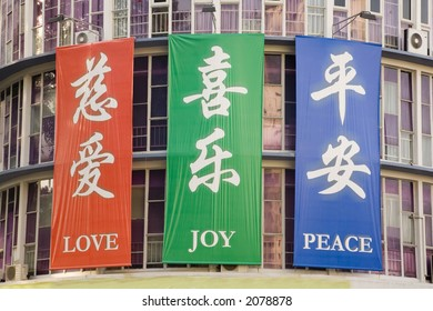Banners with the words Love Joy Peace in English and Chinese on a church in Singapore, in brilliant red, green and blue.
