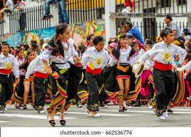 Banos De Agua Santa, Ecuador  - 29 November 2014: Group Of Unidentified Ecuadorian Kids In Traditional Colorful Costumes Dancing On Streets Of Banos De Agua Santa, South America On November 29, 2014