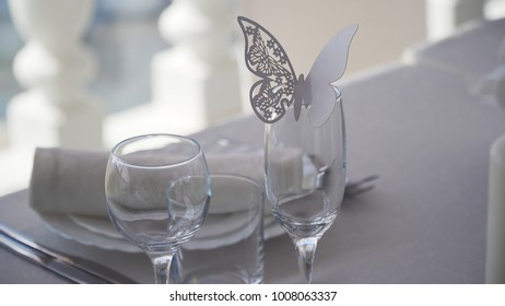 Banquet decorated table, with cutlery. Paper butterfly application on a glass. Wedding decor in the banquet hall. Serving of a festive table, plate, napkin, knife, fork. Table setting decoration