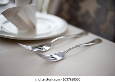 Banquet decorated table, with cutlery. Wedding decor in the banquet hall.Serving of a festive table, plate, napkin, knife, fork. Table setting decoration. Romantic Dinner or other events.