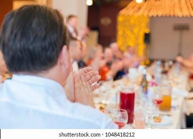 Banquet guests applaud, the men's hands, clap