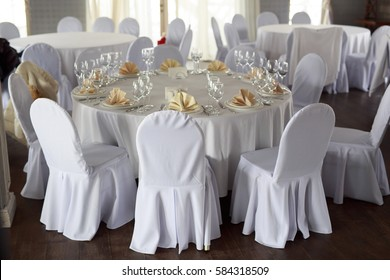 Banquet hall chairs, white tablecloth, food table, table setting, empty wine glasses, Banquet hall without people, wooden floor