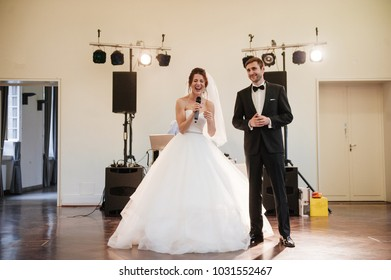 Banquet in the hall decorated with light bulbs. Presidium. Celebration. Table setting. Bride and groom. Wedding day. The bride sings a song to the bridegroom.