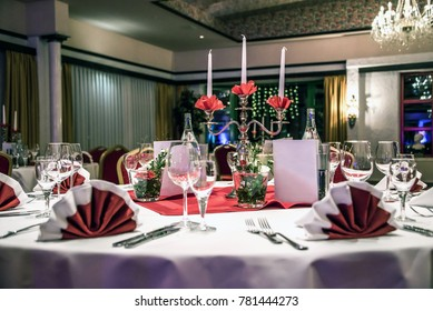 Banquet with red table setting tablecloth white dishes silver cutlery glasses and decorations white copy text space card