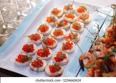 Banquet service. Sandwiches with red caviar, shrimp, hamon