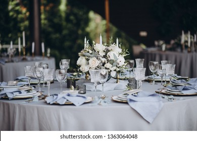 banquet table is decorated with plates, cutlery, glasses, candles and flower arrangements
