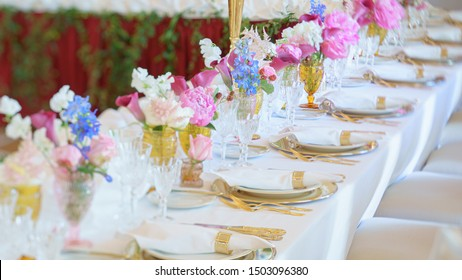 Banquet table with forks, knives, plates and flowers and berries