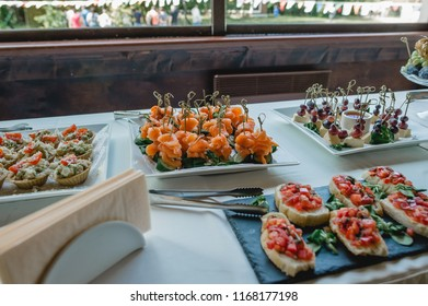 Banquet table on which a plate with salmon canapés, toast with vegetables, Caesar salad in baskets and canapés of grapes with cheese