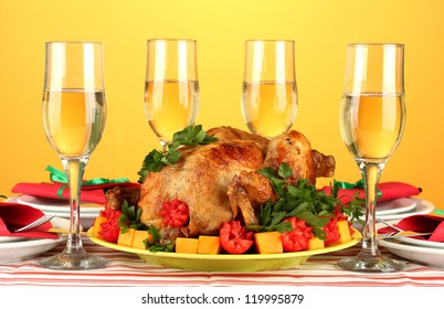 banquet table with roast chicken on orange background close-up. Thanksgiving Day