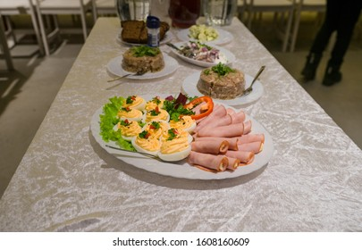 Banquet table waiting for people. Plate with filled eggs and ham rolls. Meat jelly in the background. Traditional food.