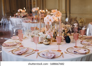 banquet tables with white tablecloths are in the hall of the old house, on the tables are flower arrangements, candles, plates with napkins, glasses and cutlery