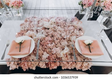Banquet. Wedding. The glass table is decorated with a lot of beautiful pale pink flowers, with white roses on plates and pastel pink napkins