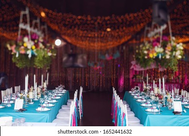 Banquet of the wedding party dinner. Luxury decor decorated tables with flowers, tableware and in turquoise pink colors. Wooden chairs with silk ribbons.
