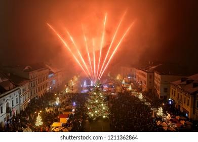 BANSKA BYSTRICA, SLOVAKIA - JANUARY 1, 2018: New Year`s Eve firework behind Christmas tree. Celebrating year 2018 in Banska Bystrica, Slovakia. Multicolor explosion on dark sky.