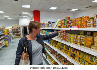 BANSKA BYSTRICA, SLOVAKIA - SEPTEMBER 29, 2017: Caucasian middle aged woman visits food store and store shelf with various kinds of pates and snacks.