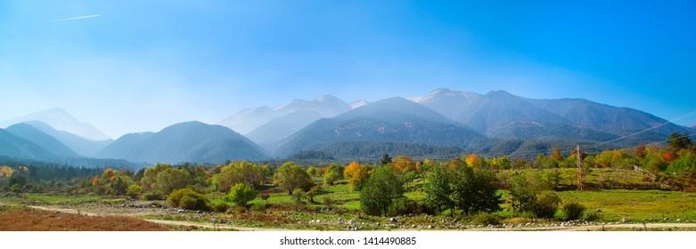 Bansko Herbstpanorama Hintergrund der Pirin-Berge, Bulgarien mit bunten grünen, roten und gelben Bäumen und Berggipfeln