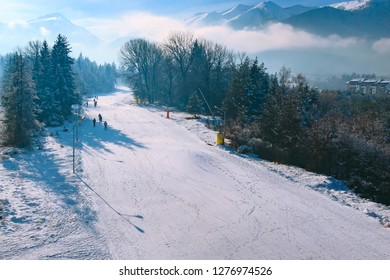 Bansko, Bulgaria aerial winter resort view with ski slope in the forest and mountains view