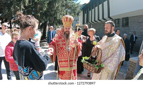 Bansko, Bulgaria - April 06, 2018: Easter parade ceremony on streets in Bansko, Bulgaria. Priests traditionally walks down the streets singing religious songs and giving Easter eggs to children