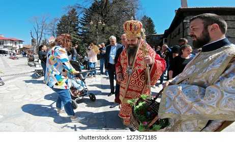 Bansko, Bulgaria - April 06, 2018: Easter parade ceremony on streets in Bansko, Bulgaria. Priests traditionally walk down the streets singing religious songs and giving Easter eggs to children