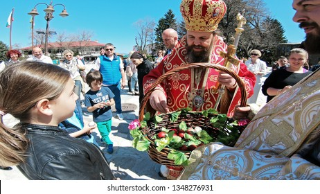 Bansko, Bulgaria - April 06, 2018: Easter parade ceremony on streets, priests and people traditionally walk down the streets singing religious songs and giving Easter eggs to children