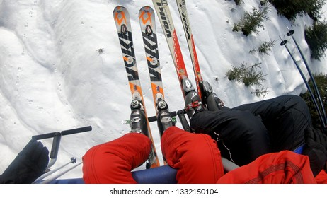 Bansko, Bulgaria - circa Feb, 2018: Close-up of skiers and snowboarders on a cable ski lift n Bansko enjoying a beautiful view of the Pirin Mountains copyspace recreation active sport seasonal concept