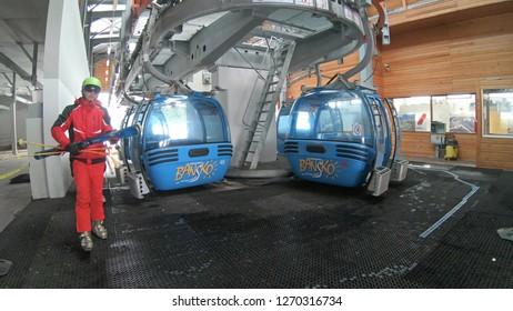 Bansko, Bulgaria - circa Mar, 2018: Skiers arriving at Banderitsa gondola ski lift station at Pirin mountain in Bansko, Bulgaria. Bansko is a most popular ski resort and world ski cup destination