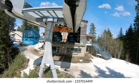 Bansko, Bulgaria - circa Mar, 2018: Skiers arriving at Banderitsa gondola ski lift station at Pirin mountain in Bansko, Bulgaria. Bansko is a most popular ski resort and world ski cup resort