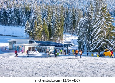 Bansko, Bulgaria - December 20, 2018: Ski resort view with mountains covered by pine trees, ski lift, people skiing