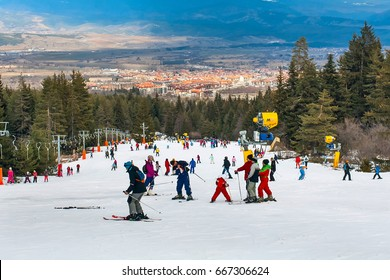 Bansko, Bulgaria - February 11, 2016: Skiers on the slope , ski lift, mountains view and Bansko town panorama