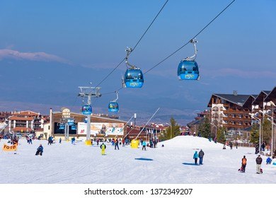 Bansko, Bulgaria - February 14, 2019: Winter ski resort Bansko, ski slope, people skiing and mountains view.
