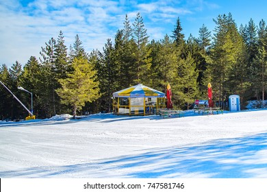 Bansko, Bulgaria - February 19, 2015:  Ski slope in Bansko, Bulgaria, pine trees, small cafe and mountains view