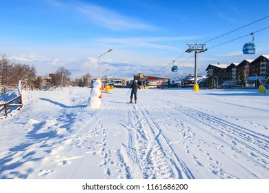 Bansko, Bulgaria - January 22, 2018: Winter ski resort Bansko with ski slope, lift cabins, people and mountains view