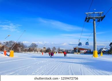 Bansko, Bulgaria - January 22, 2018: Winter ski resort Bansko with ski slope, lift cabins, people and mountains view