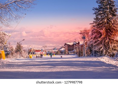 Bansko, Bulgaria - January 22, 2018: Winter sunset ski resort Bansko with ski slope, gondola lift cabins, people and mountains view