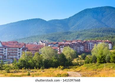 Bansko, Bulgaria - June 13, 2017: St Ivan Rilski and Panorama hotel houses and summer mountains panorama in bulgarian all season resort