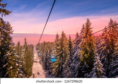 Bansko, Bulgaria winter ski resort pink sunset view, lift cabins, pine trees and snow mountain peaks