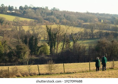Banstead Wood and Chipstead Downs Nature Reserve, Surrey, UK - February 28th 2021, Elderly couple wearing green coats enjoy sunny day and admire views during the walk at the Banstead Woods, Surrey, UK