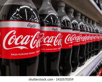 Banting, Malaysia - 19th May 2019: Light Coca Cola Bottles neatly arranged on a shelf shot with selective focus inside a Supermarket in Banting, Malaysia